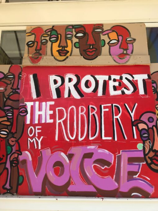 """Mural on outside of boarded up business that reads """"I Protest the Robbery of my Voice"""" with images of black and brown faces around it."""